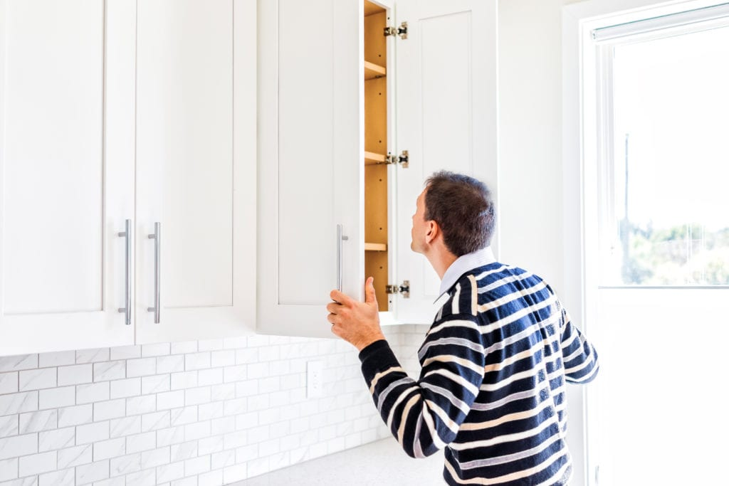 Man looking a cupboard